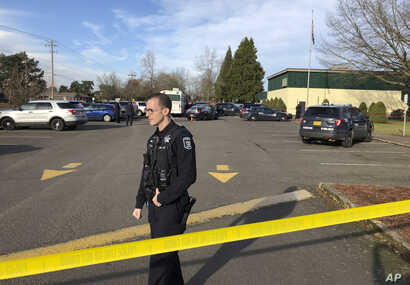 Eugene police officers stand outside the Cascade Middle School in Eugene, Oregon,  Jan. 11, 2019, following an officer-involved shooting.
