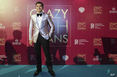 "Actor Henry Golding poses as he arrives for the red carpet screening of the movie ""Crazy Rich Asians,"" Aug. 21, 2018, in Singapore."