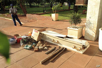 A police officer guards exhibits recovered during fuel protests and on display outside the magistrates courts in Harare, Jan. 18, 2019. Among the items was a coffin that protesters used to signify the death of Zimbabwean President Emmerson Mnangagwa'...