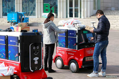 FILE - People retrieve their parcels from a JD.com driverless delivery robot in Tianjin, China, Nov. 12, 2018.