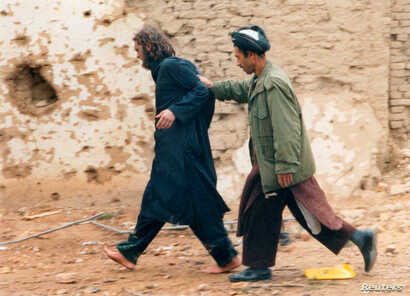 FILE - U.S.-born John Walker Lindh, left, is led away by a Northern Alliance soldier after he was captured among al-Qaida and Taliban prisoners following an uprising at the Fort Qali-i-Janghi prison near Mazar-i-Sharif, Dec. 1, 2001.