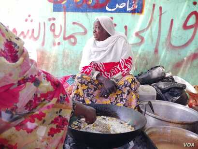 Tea seller Awadeya Mahmoud talks to a customer in Khartoum, Sudan.
