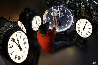 In this Thursday, Nov. 3, 2016 photo, Dan LaMoore wipes down a Shinola clock at Electric Time Co., in Medfield, Mass.