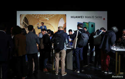 People look at display models of Huawei Mate20 smartphone series at a launch event in London, Britain, Oct.16, 2018.