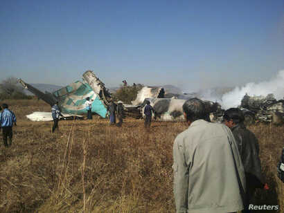 FILE - People gather at the wreckage of a Air Bagan Fokker-100 passenger jet that crashed in Heho, Myanmar, Dec. 25, 2012.