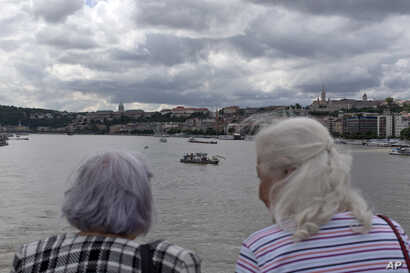 Two women watch a rescue vessel off the Margit bridge on the Danube river where a sightseeing boat had capsized in Budapest, Hungary, May 31, 2019.