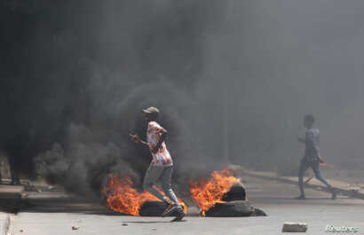 Somali demonstrators run past burning tires during protests sparked by the killing of a rickshaw driver and passenger in Mogadishu, Somalia, April 13, 2019.
