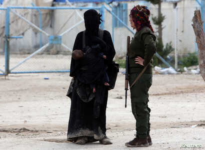 A fighter of the Syrian Democratic Forces (SDF) stands next to the wife of an Islamic State militant in al-Hol displacement camp in Syria, April 1, 2019.