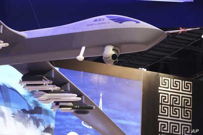 A model of a Wing Loong II weaponized drone hangs above the stand for the China National Aero-Technology Import & Export Corp. at a military drone conference in Abu Dhabi, United Arab Emirates, Feb. 25, 2018.
