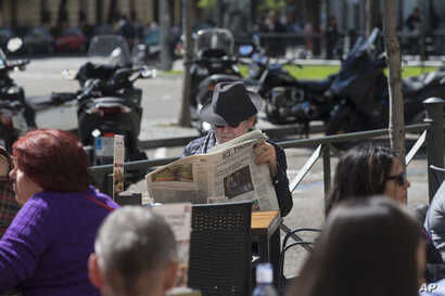 "A man reads a newspaper in a terrace bar on what's called ""The day of Reflection"" before the general elections, in Madrid, April 27, 2019. Political parties give the public a rest day from their canvassing to relax and ponder before voting Sunday."