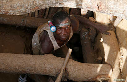 An artisanal gold miner emerges from a pit at an unlicensed mine near the city of Bouna, Ivory Coast, Feb. 11, 2018.