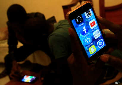 A Sudanese man holds his phone with restricted internet access to social media platforms, in Khartoum, Jan. 1, 2019.