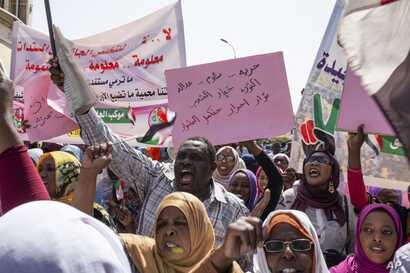 "Protesters carry posters in Arabic that say, ""Freedom, justice, and peace, and the revolution is the choice of the people,"" at the sit-in outside the military headquarters, in Khartoum, Sudan, May 2, 2019."
