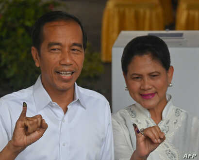 Incumbent President Joko Widodo and his wife, Iriana Widodo, display their inked fingers after casting their ballot at a polling center during the presidential and legislative election in Jakarta, April 17, 2019.