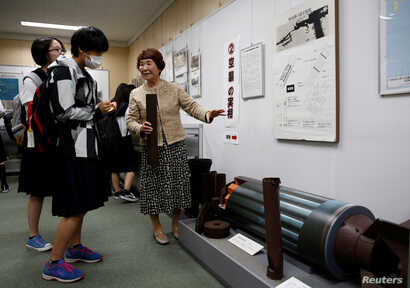 FILE - Haruyo Nihei explains to school girls visiting a museum about the March 10, 1945, U.S. firebombing in Tokyo, Japan, April 19, 2019.