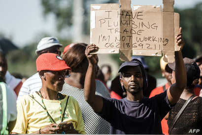 FILE - An unemployed man holds up a sign as the South African president begins his address at the Sugar Ray Xulu stadium in Clermont township, north of Durban, May 1, 2019.