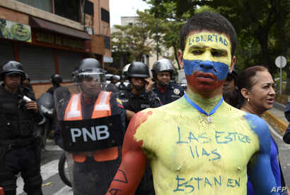 A man with his body painted in the Venezuelan national flag's colors demonstrates in front of riot police during an opposition demonstration calling for the armed forces to disobey Venezuelan President Nicolas Maduro, near La Carlota Air Base in Cara...