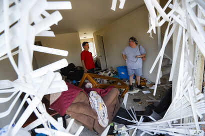 Shaun Vaine, left, and Michele Thrash, right, stand in their destroyed home at the River's Edge apartment complex, May 28, 2019, in Dayton, Ohio, the day after a tornado struck the city.