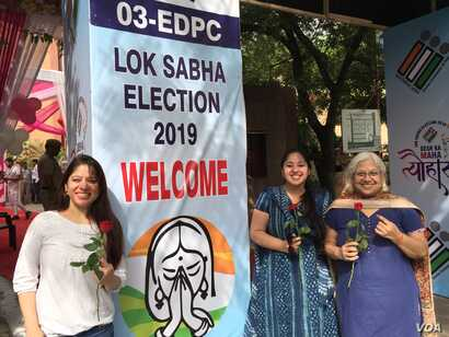 """Women emerge from a """"pink"""" polling booth set up by the Election Commission in New Delhi on voting day, May 12, 2019, as part of an initiative to marked women's empowerment."""