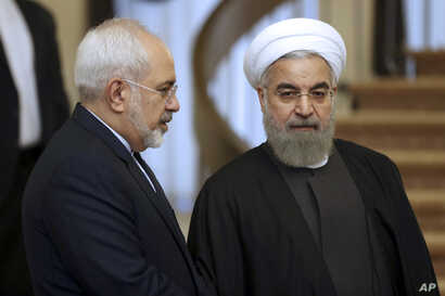 FILE - In this Nov. 24, 2015, photo, Iranian President Hassan Rouhani, right, listens to Foreign Minister Mohammad Javad Zarif prior to a meeting in Tehran, Iran.