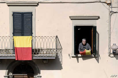 A resident holds a flag bearing the colors of the Tuscan village of Vinci, where Leonardo Da Vinci was born, April 9, 2019 in Vinci. Locals are preparing to mark the 500th anniversary of the artist's death.
