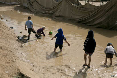 FILE - Children play in a mud puddle in the section for foreign families at al-Hol camp in Hassakeh province, Syria, March 31, 2019.