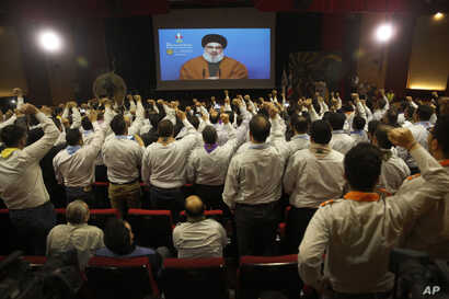 FILE - Hezbollah scouts raise their fists and cheer as they listen to a speech by Hezbollah leader Sayyed Hassan Nasrallah, via a video link, during an annual anniversary rally for Hezbollah al-Mahdi scouts, in southern Beirut, Lebanon, April 22, 201...