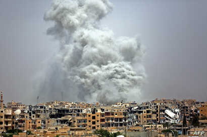 FILE - Smoke billows out from Raqqa following a U.S.-led coalition airstrike, July 28, 2017.