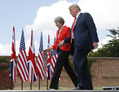 President Donald Trump and British Prime Minister Theresa May hold hands at the conclusion of their joint news conference at Chequers, in Buckinghamshire, England, July 13, 2018.