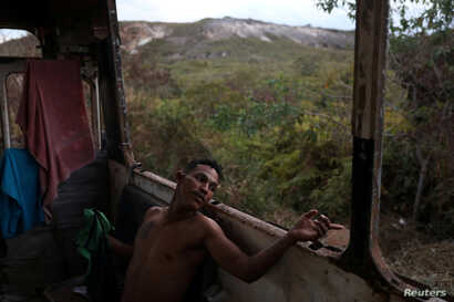 Venezuelan Hildemaro Ortiz relaxes inside of an abandoned bus in the border city of Pacaraima, Brazil, April 13, 2019.