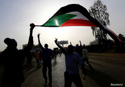 Sudanese demonstrators wave their national flag as they arrive for a protest rally demanding Sudanese President Omar Al-Bashir to step down outside the Defense Ministry in Khartoum, Sudan, April 11, 2019.