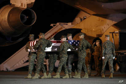 A U.S. Marine Corps carry team moves a transfer case containing the remains of Staff Sgt. Christopher A. Slutman, April 11, 2019, at Dover Air Force Base, Del.