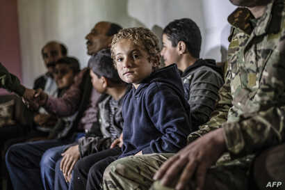 FILE - Iraqi Yazidi children rescued from the Islamic State (IS) group wait to board buses bound for Sinjar in Iraq's Yazidi heartland, April 13, 2019.