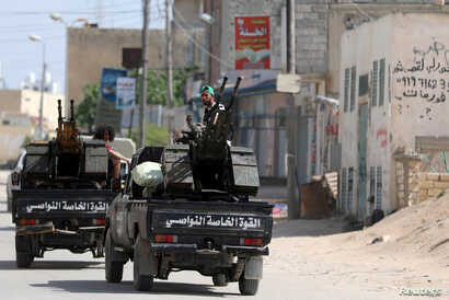 Members of Libyan internationally recognized pro-government forces ride in military vehicles on the outskirts of Tripoli, Libya, April 10, 2019.