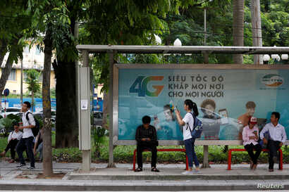 FILE - Internet users browse internet near an advertising billboard for 4G connection service at a bus-stop in Hanoi, Vietnam.