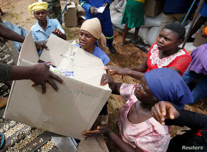 FILE - Victims of Cyclone Idai receive food aid at Siverstream Estates in Chipinge, Zimbabwe, March 24 ,2019.
