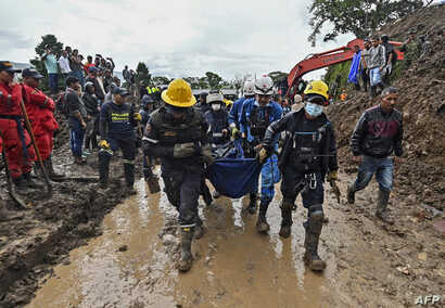 Rescue workers carry a corpse after a landslide in Rosas, Cauca department, in southwestern Colombia, April 21, 2019.