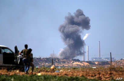 Palestinians look at smoke billowing from the site of an Israeli air strike on a Hamas' military site in Beit Lahia near the border between Israel and the Gaza Strip, east of Jabalia on May 14, 2018.