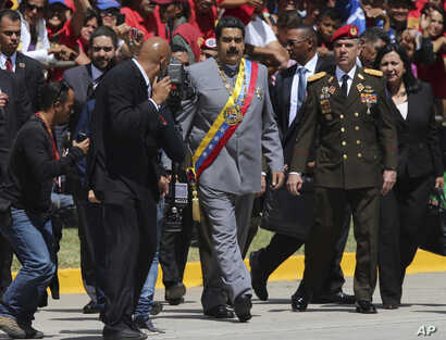 FILE - Gen. Ivan Hernández, head of both the presidential guard and military counterintelligence, right, keeps an eye on Venezuela's President Nicolas Maduro as he arrives for a military parade at Fort Tiuna in Caracas, Venezuela, Feb. 1, 2017.