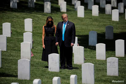 "U.S. President Donald Trump and first lady Melania Trump stand among the graves during the annual ""flags in"" ceremonies before Memorial Day as the president visits Arlington National Cemetery in Arlington, May 23, 2019."