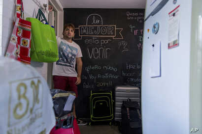 """FILE - Tomas Ruiz poses for a portrait by a chalkboard covered in the Spanish messages for him: """"The best is yet to come,"""" and """"I love you very much, I'm gonna miss you, Happy 2019"""" at his mother's house in Buenos Aires, Argentina, April 2, 2019."""