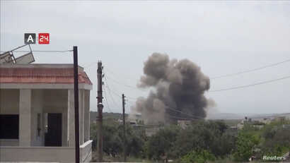 FILE - A barrel bomb dropped from a helicopter explodes in Karsaa, Idlib province, Syria, May 7, 2019, in this still image taken from a video on May 9, 2019.