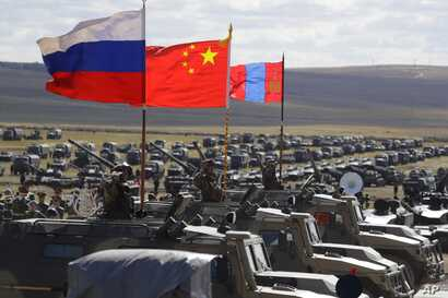 "FILE - Russian, Chinese and Mongolian national flags set on armored vehicles develop in the wind during a military exercises on training ground ""Tsugol, south-east of the city of Chita during the military exercises Vostok 2018 in Eastern Siberia, Rus..."