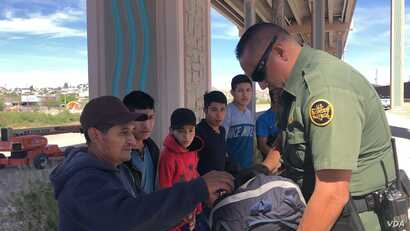 U.S. Customs Border Patrol agents check the migrants' bags. This group of Guatemalan migrants, which includes a child,  wait to be processed by an agent, April 9, 2019. C. Mendoza/VOA News