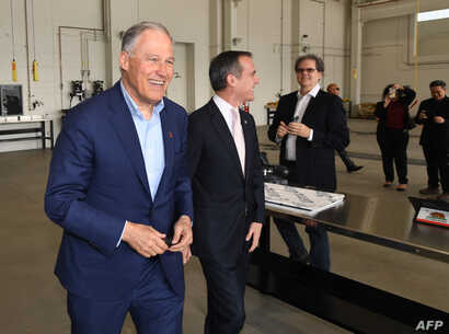 Democratic presidential hopeful Jay Inslee, who is the governor of Washington state, walks beside Los Angeles Mayor Eric Garcetti during a tour of the Los Angeles Department of Transportation bus depot in Los Angeles, May 3, 2019.
