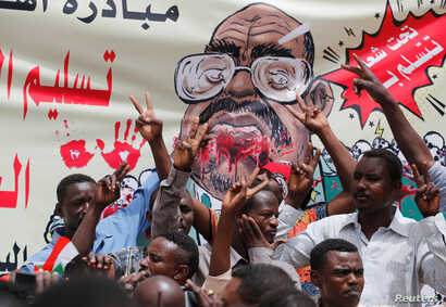 Protesters shout slogans by a banner depicting former Sudanese President Omar al-Bashir, in front of the Defense Ministry in Khartoum, Sudan, April 19, 2019.