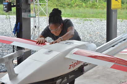 Zipline flight operator Josephine Fianu gets a drone ready for takeoff from the Omenako drone center. So far, four health centers are using the service in Ghana. (S. Knott/VOA)