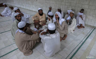 FILE - Pakistani religious students and teachers attend a discussion session at the Ganj Madrassa in Peshawar.