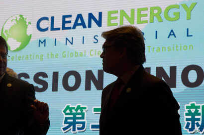 """U.S. Energy Secretary Rick Perry is silhouetted near the words """"Clean Energy"""" during a photo session after the opening ceremony of an international clean energy conference in Beijing, June 7, 2017."""