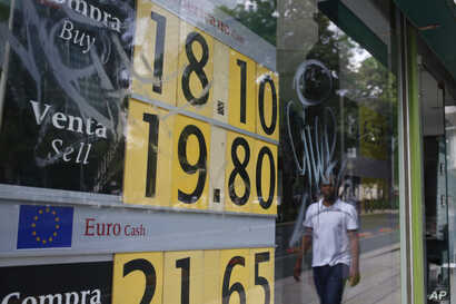 A stock monitor shows exchange rates on a storefront in Mexico City, Mexico, May 31, 2019, a day after U.S. President Donald Trump's threat to impose a 5% tariff that could rise substantially on all Mexican imports. The peso dropped more than 3% against t